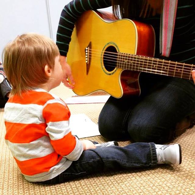Child Strumming Guitar in Music Therapy
